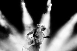 Tiago Iorc se apresenta pela primeira vez em Gramado. Em foto preta e branca, Tiago Iorc canta e toca violão no palco de um de seus shows