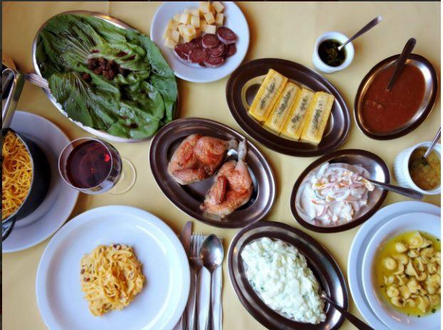 Desfrute as delícias da Galeteria Nanoma, em Canela. Na foto, uma mesa recheada de pratos deliciosas, com galeto, salada, polenta, massas e etc