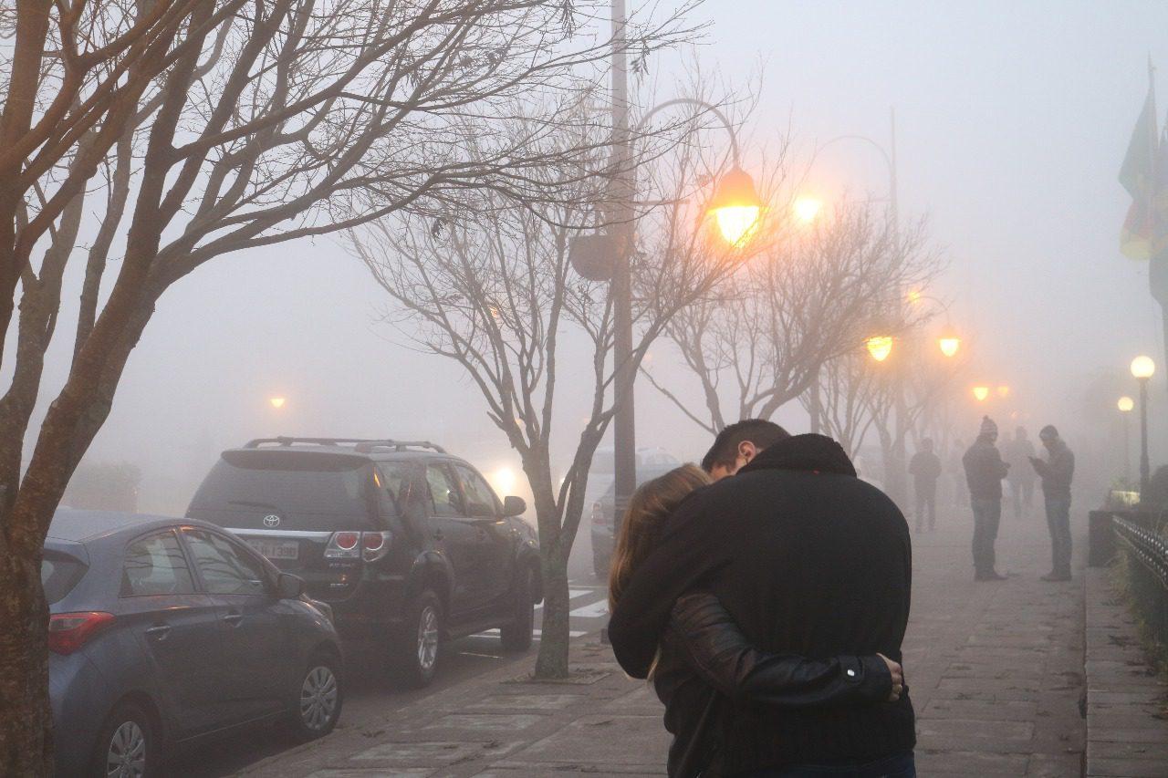 Na foto, um casal se beija pelas ruas de Gramado, curtindo a serração de um dia frio