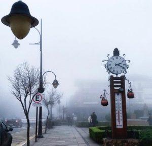 Muita neblina, mostra uma calçada com uma árvore sem folhas, um relógio e um termômetro.